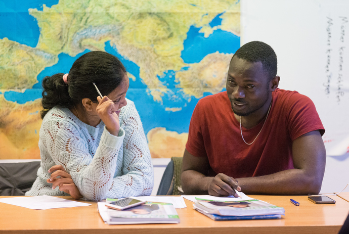 Recent immigrants Swapna (left) from India and Richard from Ghana work on exercises in their German class at the United Methodist Church of the Redeemer in Bremen, Germany. Photo by Mike DuBose, UMNS.
