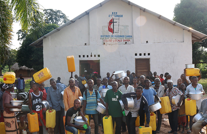 Beneficiaries of supplies stand in front of the local church in the Kasongo-Samba District. In the East Congo Episcopal Area, Connexio, a network for service of The United Methodist Church of Switzerland and France, has helped the episcopal area provide aid to Kabambare territory residents who fled following the insurrection of Mai Mai Malaika rebels. Photo by Judith Osongo Yanga, UMNS.