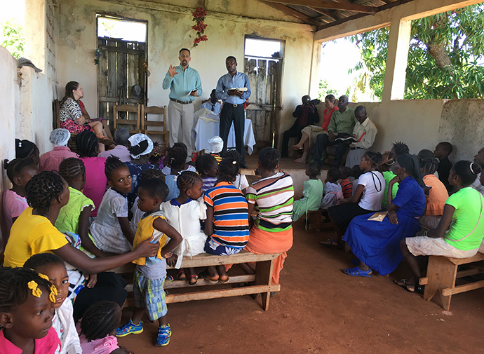 """The Rev. Matt Henson (standing, left, in green shirt) speaks in a church in Sobier, Haiti. Henson, president of National Association of United Methodist Evangelists, hopes to increase awareness of the association and in turn help the church connect new people with the """"old, old story."""" Photo courtesy of The Rev. Matt Henson."""