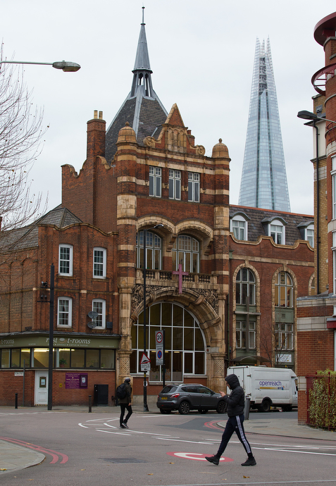 Bermondsey Central Hall Methodist Church serves a diverse congregation of about 250 and houses the South London Mission, which has been supporting the community since 1889. The modern London Shard skyscraper rises behind the church.