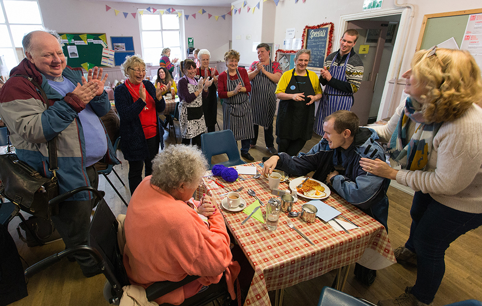 Community members, staff and volunteers wish Craig Kirwin (seated, right) a happy birthday during the twice-weekly community café at Wharton and Cleggs Lane Church and Community Centre in Little Hulton, England. Photo by Mike DuBose, UMNS.