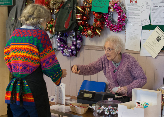 Muriel Reade (right), 88, serves as cashier and treasurer during the community café. Photo by Mike DuBose, UMNS.