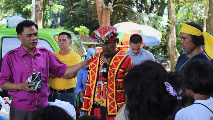 Bishop Rodolfo A. Juan (left) prays for a leader (red vest) at a camp for displaced people in Malaybalay, Philippines, in 2017. On Feb. 22, Juan made contacts on behalf of a team of five — including two missionaries with the United Methodist Board of Global Ministries— who were briefly detained at a police checkpoint in Koronadal City, Philippines. File photo courtesy of Dan Ela.