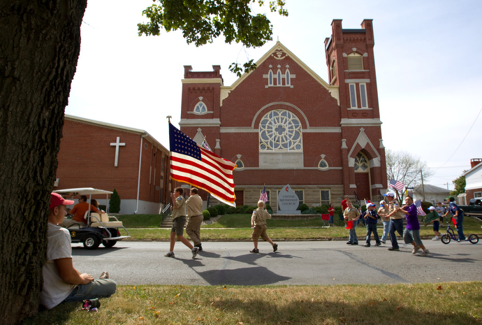 Boy Scouts from Troop 222 march in front of Leipsic (Ohio) United Methodist Church in 2010 during the parade that kicks off the town's annual Fall Festival. Watching the parade, at left, is Luke Lammers. File photo by Mike DuBose, UMNS.