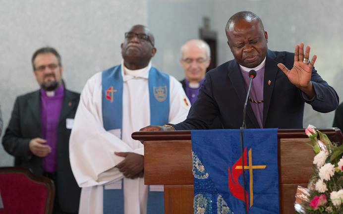 Bishop Mande Muyombo (right) prays at Canaan United Methodist Church in Abidjan, Côte d'Ivoire, where members of the Standing Committee on Central Conference Matters worshipped during their meeting. One issue before the group is where to place five new bishops in Africa. Mande, who serves in Democratic Republic of Congo and is the denomination's most recently elected bishop, is joined by (from left) Bishops Harald Rückert, Gregory Palmer and Patrick Streiff. Photo by Mike DuBose, UMNS.
