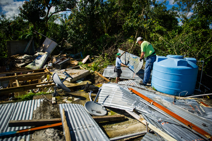 Nick Shelly (left) and the Rev. Mike Evans clear damaged metal roofing from a storm-devastated home in Hatillo before new construction begins. Photo by Matt Brodie.