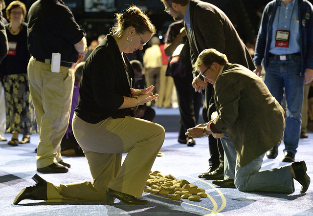 """A delegate picks up and holds a stone in the center aisle during an April 27 """"Act of Repentance toward Healing Relationships with Indigenous Peoples"""" at the 2012 United Methodist General Conference in Tampa, Florida. A UMNS photo by Paul Jeffrey."""