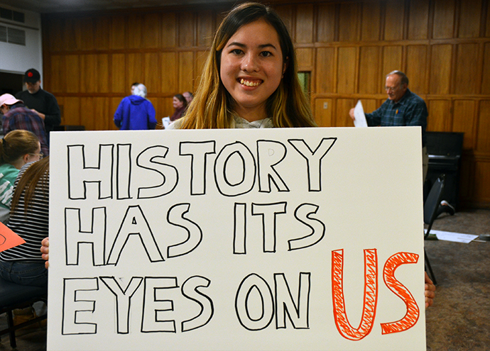 """Olivia Greene, a member of National United Methodist Church in Washington, was part of an overnight """"lock-in"""" there on March 23, the day before the Walk for Our Lives. She was working on a sign that read, """"History has its eyes on us."""" Photo by Erik Alsgaard."""