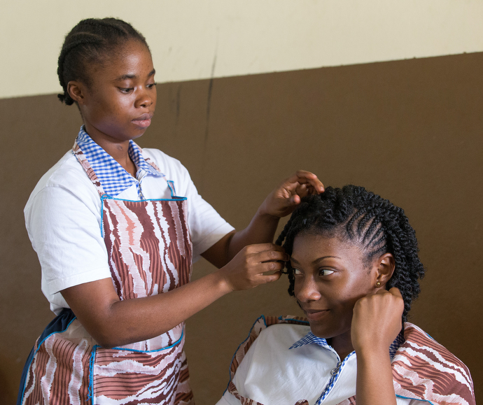 Kamonda Gualla (right) has her hair done by fellow student Marie Touhé in a cosmetology class at the United Methodist Anyama School in Abidjan. Photo by Mike DuBose, UMNS.