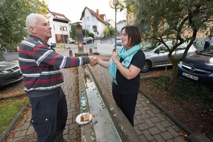 Rev. Heike Miller (right) visits with Dieter Kugelmann outside the United Methodist Church in Lorsbach, Germany, during Café Gegenüber, a weekly gathering for coffee, cake and conversation. Photo by Mike DuBose, UMNS.