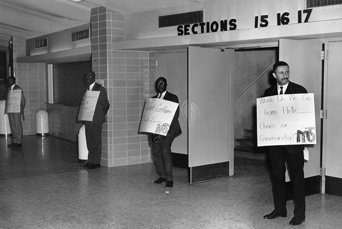 """""""Where do we go from here… Chaos or Community?"""" appears on the sign held by the Rev. Gilbert H. Caldwell by the entrance to the plenary for the 1968 Uniting Conference in Dallas. The phrase is the title of the Rev. Martin Luther King Jr.'s final book, and a reminder of the church's ongoing call to confront racism. Photo courtesy of the Archives and History."""