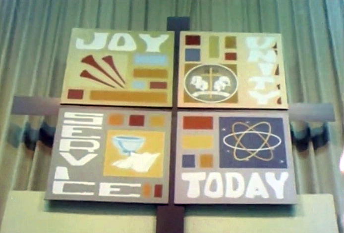 A banner proclaiming JOY, UNITY, SERVICE, TODAY hangs above the altar in the plenary space of the 1968 Uniting Conference in Dallas. Screenshot from 1968 Television, Radio and Film Commission video.