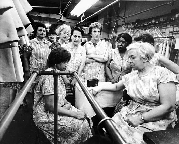 Garment workers at the Abe Schrader Shop listen to the funeral service for the Rev. Martin Luther King Jr. on a portable radio, April 8, 1968. Photo courtesy of Kheel Center, Cornell University, via Wikimedia Commons.