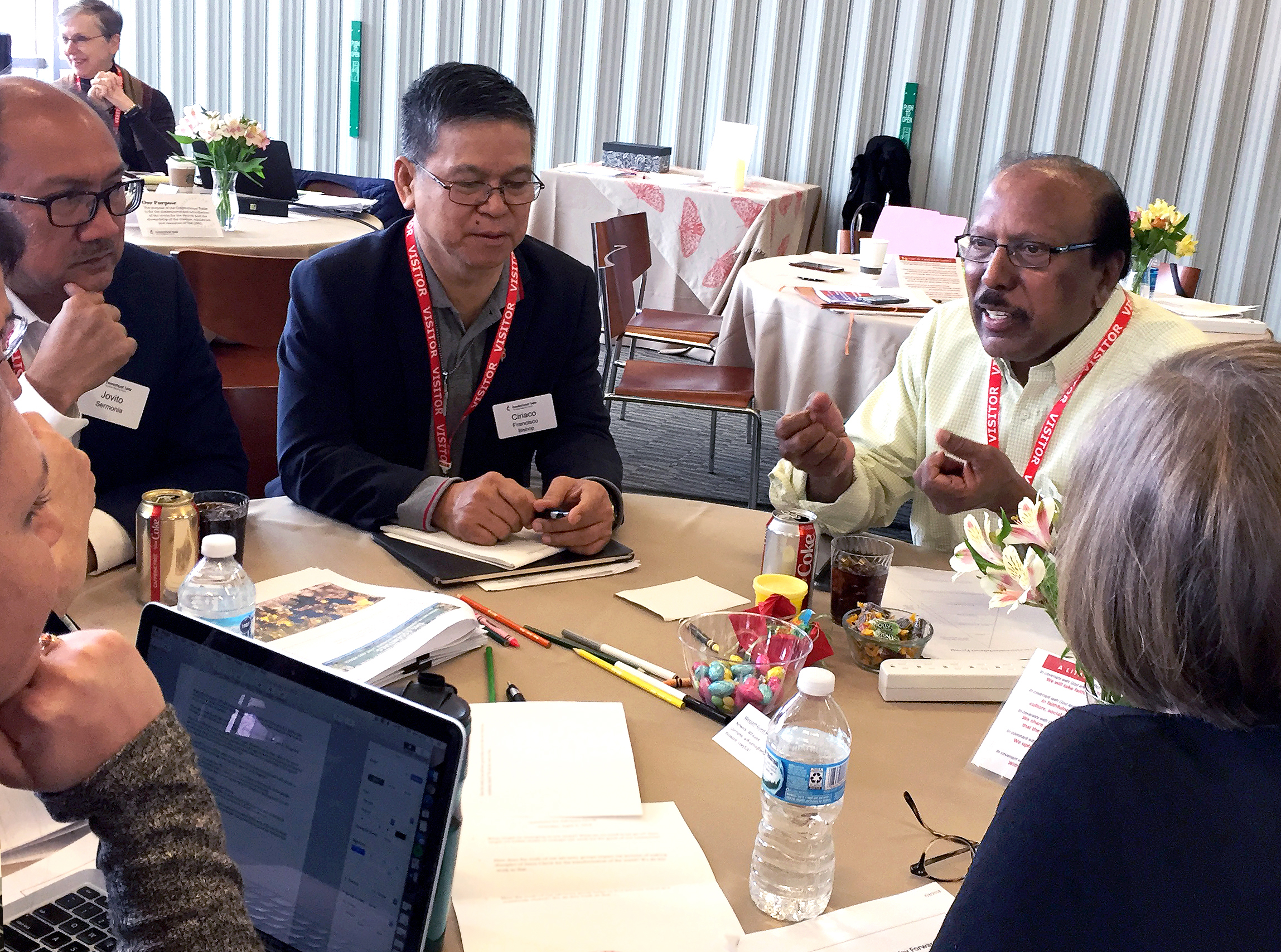 Members of The Connectional Table talk in a small group after a presentation on the Way Forward Commission. From left facing the table are members Jovito Sermonia of the Philippines, Bishop Ciriaco Francisco of the Philippines and the Rev. Jacob Dharmaraj of New York. Photo by Heather Hahn, United Methodist News Service.