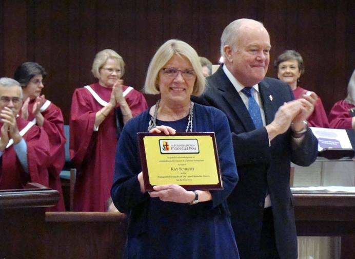 Kay Schecht, standing with Bishop Mike McKee, accepts the Foundation for Evangelism's Distinguished Evangelist Award during the April 8 worship service at Plymouth Park United Methodist Church, in Irving, Texas. Photo by Bill Fentum.