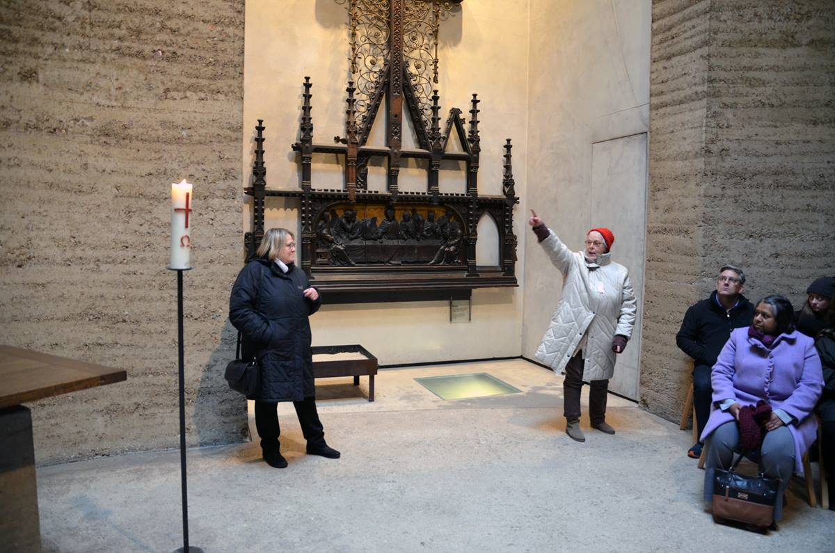 In the Chapel of Reconciliation at the Berlin Wall Memorial, tour guide Christiane Schmidt (right) explains to those gathered how the altarpiece from the original Church of Reconciliation was damaged when the building was blown up by the East German government in 1985. The piece survived the demolition and now hangs in the new chapel. Bishop Rosemarie Wenner of Germany (left) looks on. Photo by Klaus U. Ruof, UMNS.
