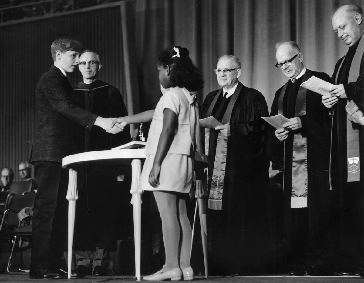 Robert O. Tupper II, representing the Evangelical United Brethren, and Rhonda Renfro, representing the Methodist Church, were the two children chosen to shake hands as part of the ceremony uniting the two denominations into The United Methodist Church, on April 23, 1968, in Dallas. Renfro, now 57, says event organizers wanted the symbolism of a black child and white child shaking hands to reinforce the new denomination's commitment to racial reconciliation. Photo courtesy of the United Methodist Commission on Archives and History.
