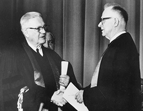 Evangelical United Brethren Church Bishop Reuben H. Mueller (left) and Methodist Bishop Lloyd C. Wicke join hands on April 23, 1968, symbolizing the merger between the two denominations.1968 file photo courtesy of the United Methodist Commission on Archives and History