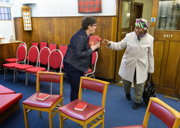 The Rev. Janet Corlett (left) welcomes Frances Dakowa for a prayer and praise service at Bermondsey Central Hall Methodist Church. Photo by Mike DuBose, UMNS.