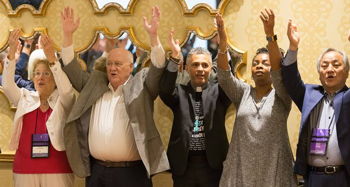 "Attendees at the United Methodist Council of Bishops meeting in Chicago join in the ""Praying Our Way Forward"" closing worship service. The council deliberated on its final proposals to next year's special General Conference that will address decades of division over how the church should minister with LGBTQ individuals. From left are: Jolynn Lowry, Bishop J. Michael Lowry, the Rev. Alex da Silva Souto and Bishops Cynthia Moore-Koikoi and Hee-Soo Jung. Photo by Mike DuBose, UMNS."