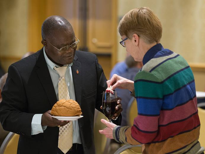 Bishop José Quipungo of the East Angola Area (left) and Sue Laurie of Love Prevails, an unofficial group that advocates for equality of LGBTQ individuals, share Holy Communion during the United Methodist Council of Bishops meeting in Chicago. Photo by Mike DuBose, UMNS.