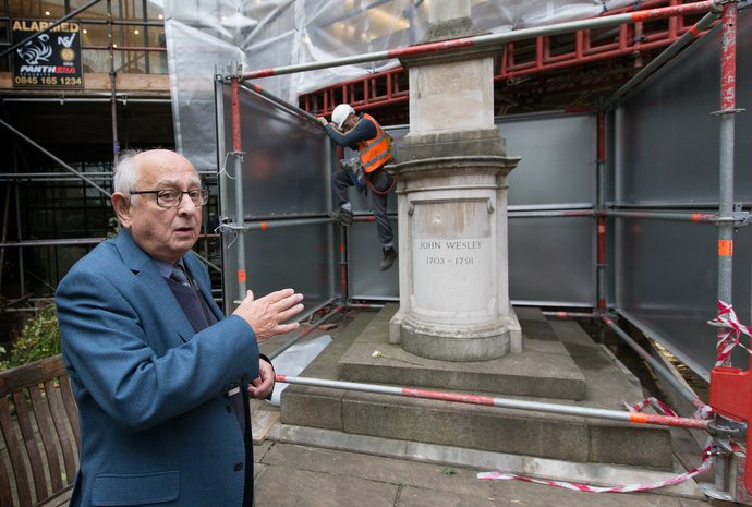 """Tour guide Allen Steel points out John Wesley's tomb in the garden at Wesley's Chapel while a worker climbs down from scaffolding erected to protect the historic site from encroaching construction in the area that has become known as the """"silicon roundabout"""" because of the presence of high-tech industries. Photo by Mike DuBose, UMNS."""