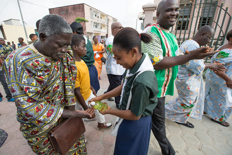 United Methodist Scouts from the Ivoirian Scouting Federation dispense hand sanitizer to parishioners arriving for worship at Temple Bethel United Methodist Church in the Abobo-Baoule neighborhood of Abidjan.