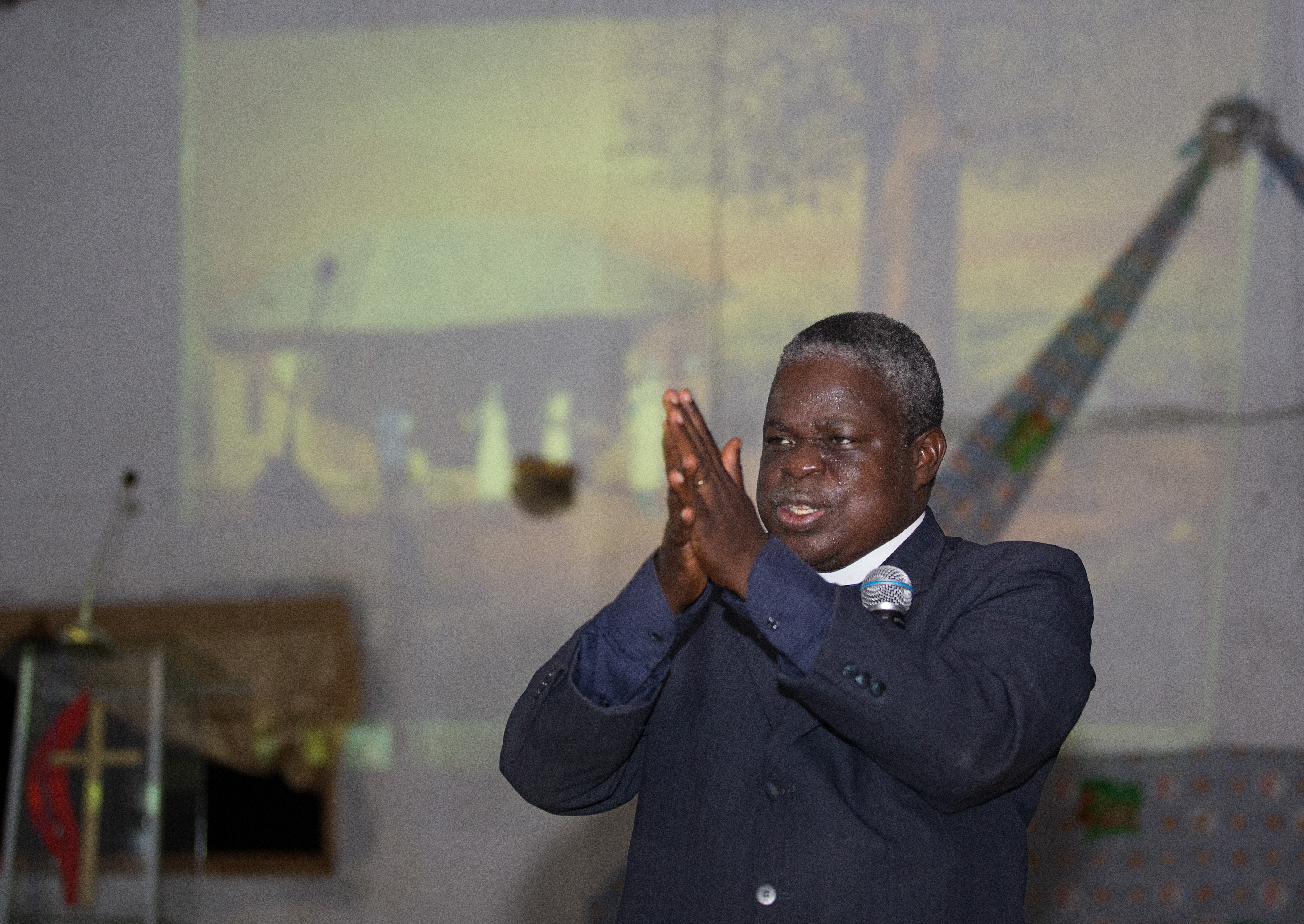 """The Rev. Marcel Sachou demonstrates the proper technique for hand-washing while showing a video about the prevention of Ebola at the United Methodist Church in Sassandra. The animated video, """"Ebola: A Poem for the Living,""""  was created by Chocolate Moose Media and mobile-health-education innovator iHeed in collaboration with United Methodist Communications."""