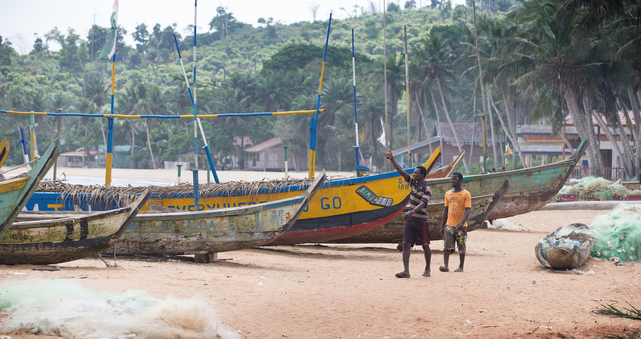 Fishermen walk past their boats in Monogaga.