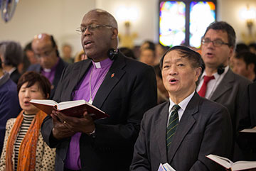 The Rev. Bao Jiayuan (right foreground) is flanked by United Methodist Bishop Warner Brown (left foreground) and Thomas Kemper of the denomination's Board of Global Ministries during worship at Chongwenmen Church in Beijing, China. Bao's work with the China Christian Council has made him the council's good-natured ambassador to Christians and interfaith representatives worldwide.