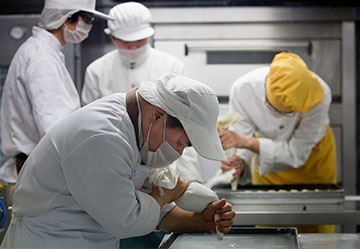 Student bakers, under the supervision of a special education teacher (wearing yellow) create pastries at the Amity Bakery in Nanjing, China.