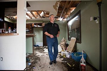 The Rev. D.A. Bennett surveys tornado damage at the home of parishioner Trent Steward in Moore, Okla.