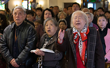 Shen Lu de (right foreground) joins with fellow worshippers to sing a hymn at Chongwenmen Church in Beijing. The church was established in 1870 by U.S. Methodists and was then known as Asbury Church.