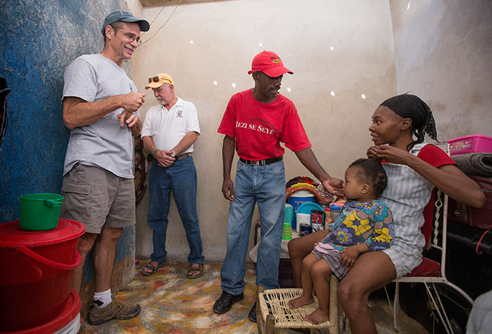 The Rev. Tom Vencuss (left) and Bill Borah visit with Jean Claude Degazon (center) in his rebuilt home. Juliet Degazon (right) and Nana, 2, are among 15 family members who live in the home.