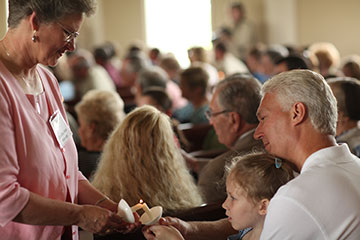 The Rev. Dorothy Ann Webster (left) lights candles during the first worship service at Ford's Chapel United Methodist Church in Harvest, Ala., after a tornado damaged the sanctuary in April 2011. A UMNS file photo by Kathleen Barry.