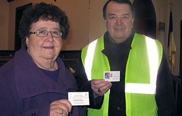 The Rev. Wilma Bone (left), then pastor of Henryville (Ind.) United Methodist Church, and Indiana Area Bishop Michael Coyner display their emergency-identification cards. Bone found her card was the key to gaining entry into Henryville after a March 2, 2012, tornado destroyed much of the town. A UMNS file photo.
