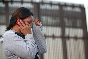 Nancy, who was deported from the U.S. after a traffic violation, cries as she speaks with her mother in Los Angeles from the Mexican side of the massive border fence in Tijuana.