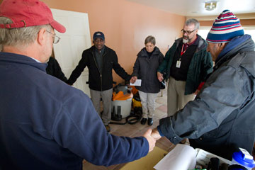 The Rev. Tom Hazelwood (second from right) of the United Methodist Committee on Relief leads a prayer at a home damaged by floodwaters from Hurricane Sandy in Massapequa, N.Y. A UMNS photo by Mike DuBose.