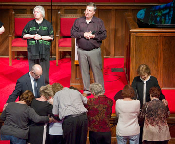 Bishop Debra Wallace-Padgett (right) and the Rev. Bob Alford pray with parishioners during the closing hymn.