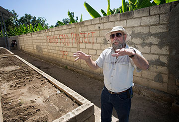 Warren McGuffin shows the raised-bed garden where okra has been planted at the Thomas Food Project.