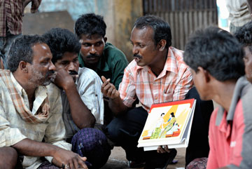 Simon Charles, an educator with the Madras Christian Council of Social Service, meets with fishermen at the dock in Chennai, India, in March 2010 to explain HIV and AIDS.