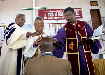 Bishops of the United Methodist Church in Angola lay hands on a new pastor during a 2006 ordination service at the West Angola Annual Conference at the Icolo e Bengo United Methodist Church in Luanda.