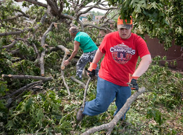 Volunteers Jacob Burrow (front) and Mark Swyden clear trees downed by the tornado in Joplin, Mo., in May 2011. In 2011, volunteers organized through the Missouri Conference contributed 16,371 hours to Joplin's recovery.
