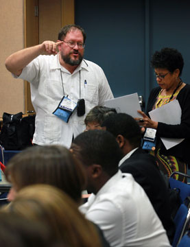 Donald Reasoner, General Conference staff, instructs a group of interpreters during the 2012 United Methodist General Conference in Tampa, Fla. To his right is Keila Guimaraes with the Portuguese language interpretation team.