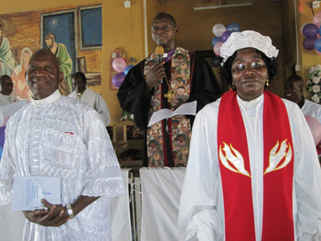 Bishop John Yambasu (in background) presents the Rev. Mariama Bockari (right), supported by husband, the Rev. David Bockari (left), to the Makeni congregation upon her induction as district superintendent.