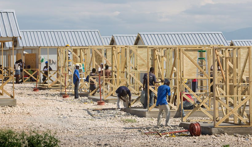 Construction workers erect homes at Camp Corail, outside Port-au-Prince. Housing, both temporary and permanent, remains a key issue as Haiti rebuilds.