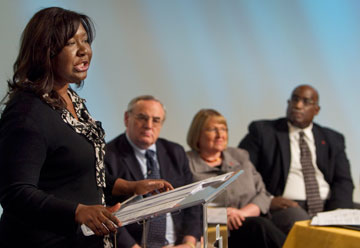 Erin Hawkins (left) addresses the summit. Behind her, from left, are Bishops Larry Goodpaster, Rosemarie Wenner and Gregory Palmer.