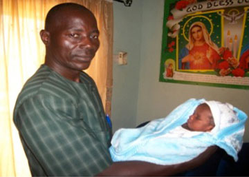 Coordinator Simon Benjamin holds a 2-day-old baby boy whose mother died.
