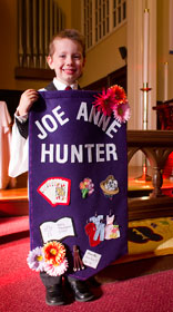 Luke Altman, 4, holds a banner honoring Joe Anne Hunter.