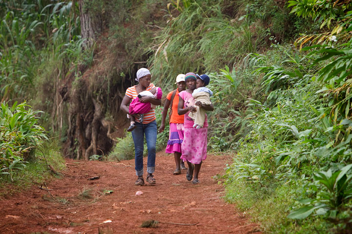Mothers carry their children down a muddy trail after a visit to the Methodist Churchs health clinic in Furcy.